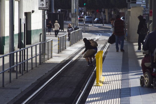 A young man jumps off the platform and onto the track at the Pico Station.