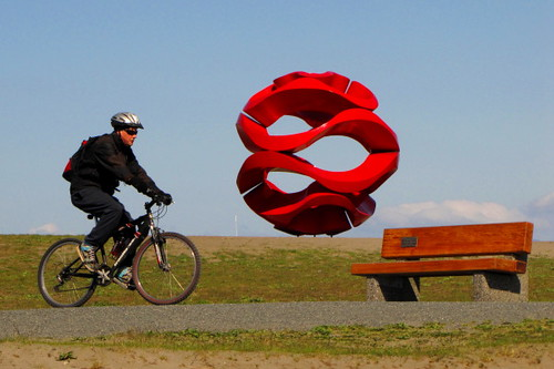 Cyclist passes by public art object at Garry Point Park