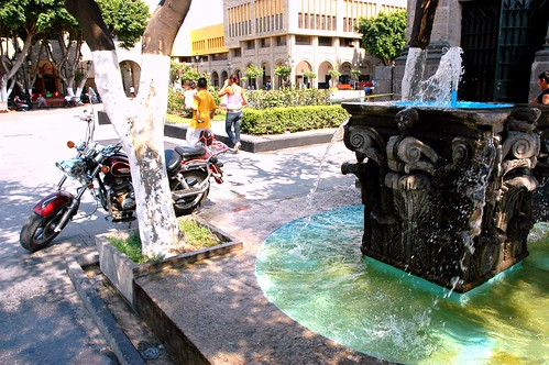 Motorcycle and couple with child + trailing spray of the brilliant turquoise classical Corinthian capitol stone water fountain, windy Central square, Guadalajara, Jalisco, Mexico by Wonderlane