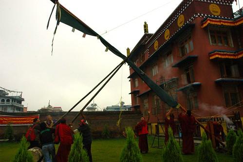 X, lowering the Tibetan Buddhist prayer flag, Tharlam Monastery, Boudha, Kathmandu, Nepal