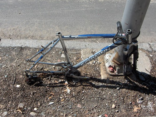 Bicycle without wheels, seat, or handlebars, sinking into the ground.