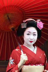 Maiko 'Katsuru' in Spring Rain (Marie Eve K.A. (away..)) Tags: red portrait people woman color colour beautiful beauty japan lady umbrella canon rouge japanese kyoto 85mm maiko geiko geisha kawaii kimono  planar   carlzeiss   kanzashi geishagirl   katsuru   kamishitiken