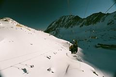 Nick and Craig on the lift (Ed.ward) Tags: shadow sky holiday snow mountains alps film austria wire chair rocks skiing lift superia nick cable craig zellamsee chairlift drift 2010 nikonf80 fujisuperia kaprun kitzsteinhorn fb:uploaded=true nikkor20mmf28afd geo:lat=47205364 geo:lon=12684129