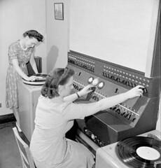 Women workers select piped music to play in the central control room of a Montreal factory. / Des ouvrières choisissent des airs de musique pour les diffuser dans la salle de commande centrale d'une fabrique de Montréal.