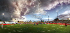 Hooray Parallax (Philerooski) Tags: sunset sky people panorama game sports field grass clouds photoshop canon wonderful lights washington amazing fantastic colorful track state stadium pano crowd wa runners athletes bleachers invite brilliant meet hdr highdynamicrange warmingup astroturf stands trackandfield pasco trackmeet tricities stadiumlights 3xp sportingevent photomatix pascoinvite edgarbrownstadium