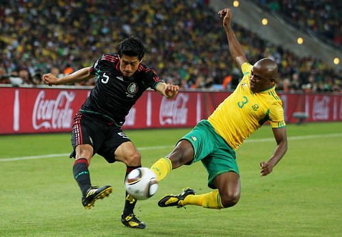 Tsepo Masilela of South Africa challenges Ricardo Osorio of Mexico during the 2010