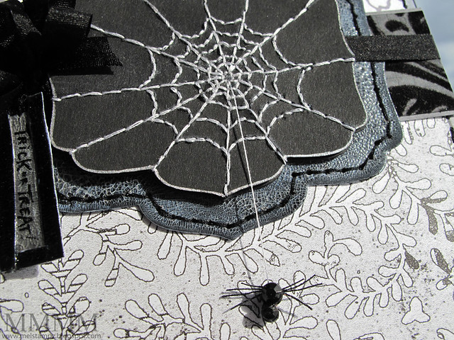 stitched spider web with swinging spider hanging by a thread