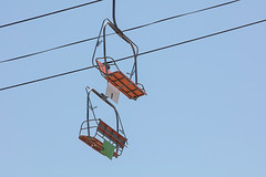 Chairlift at an amusement park (Transient Eternal) Tags: aeriallift cablechair carnivalride chairlift doublechair elevated elevatedpassengerropeway frame glide liftdevice lifts orange peoplemoveramusementpark plastic seat skilift skiinglift steelcable transport urbantransport