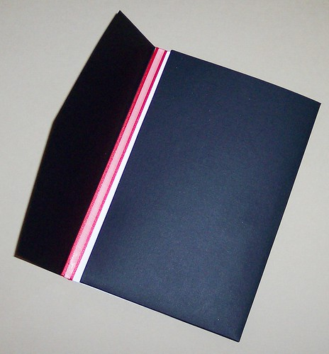 A black pocket folder with red ribbon