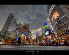 Shibuya Sunset (WilliamBullimore) Tags: road windows sunset sky people signs japan clouds buildings japanese tokyo evening technology dusk shibuya starbucks highrise intersection roads crowds futuristic pedestriancrossing kattun shibuya109 starbuckscoffee canonefs1022mmf3545usm highrisebuildings tohoshinki hisamitsu electronicsigns canonef1635mmf28liiusm canonrc1wirelessremote manfrotto190xbtripod manfrotto322rc2heavydutygripballhead ichimarukyu