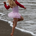 Cute+Little+Girl+in+Pink+Dances+on++Beach+during+the+Kite+Festival.