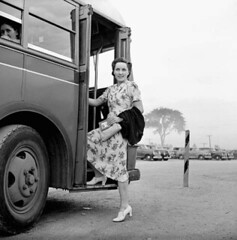 Mrs. Jack Wright boards a bus on her way to work at a munitions factory. / Mme Jack Wright monte dans un autobus pour aller travailler dans une fabrique de munitions (BiblioArc