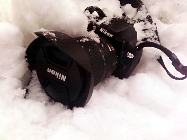 A DSLR camera half buried in snow.