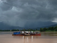 Crossing the Mekong river to Champasak (Bn) Tags: topf50 sinister route13 darkclouds rainyseason mekongriver champasak 50faves ferrycrossing riverscene champasakprovince rainymonsoon mekongferry wildestrainyseason awoodenplatform fullyloadedferry crossingthemekong ferryatchampasak travelingisatleasthalfthefun largeraft raininginthemountains stormabovethemountains