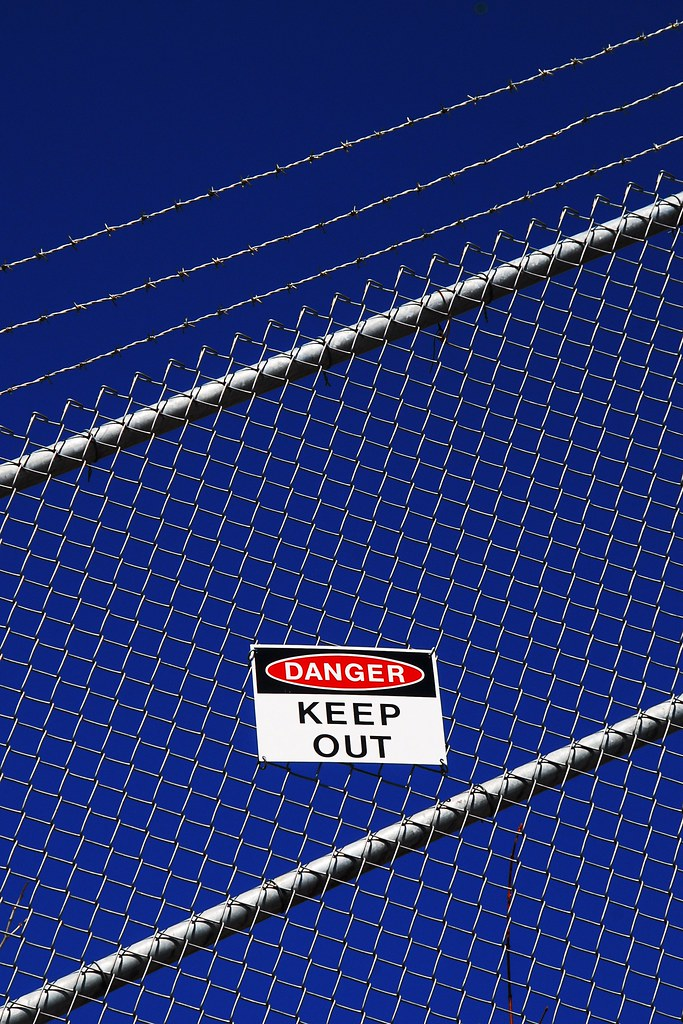 A keep out sign on a fence, with barbed wire, against a deep blue sky.