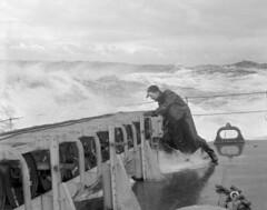 Sailor checking the stowage of depth charges at the stern of HMCS Matane in heavy seas off Bermuda, 1944 / Matelot qui vérifie l'arrimage des grenades sous-marines à la poupe du NCSM Matane, sur une mer agitée, au large des Bermudes, 1944