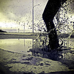 Day 21 *Puddle Jumping* (Michelle Elaine.) Tags: road street blue portrait sky bw selfportrait canada reflection cute art water oneaday rain clouds self canon vintage dark square fun puddle outside one jump lomo whimsy alone glow moody play mud autoportrait suburban action ripple joy navy naturallight dirty spray sparkle sidewalk nostalgia reflect sp freeze crop getty imagination recreation 365 fascination splash timer curb leap vignette tone whimsical actions selfie coloraccent project365 365days coffeeshoplomoaction sparkle1challenge sparkle1