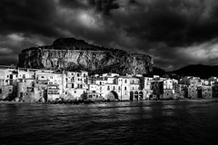 Cefal (Philipp Klinger Photography) Tags: city travel italien houses light shadow sea sky bw italy sun white house mountain storm black beach nature water rain weather rock clouds reflections landscape island bay coast town blackwhite nikon rocks europa europe mediterranean italia hill natur medieval shore sicily philipp italie rocca sicilia mediterraneansea cefalu larocca klinger sizilien sicilie cefal d700 dcdead vanagram