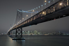 The Bay Bridge and SF Revisited (Matt Granz Photography) Tags: ocean sf sanfrancisco california ca city longexposure blue wallpaper vacation skyline architecture night clouds reflections dark island lights bay nikon downtown cityscape waterfront treasureisland skyscrapers pacific perspective sigma landmark coittower baybridge yerbabuena holidaylights hdr highdynamicrange flares desktopimage transamericabuilding d90 sigma1850mm embarcaderro starflares