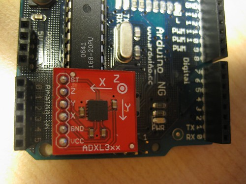 [Analog Devices' ADXL330 accelerometer on a Sparkfun breakout board next to the pins on an Arduino NG to which the board connects.]