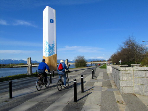Cyclists pass by the Richmond Olympic Oval sign post along the Middle Arm Greenway