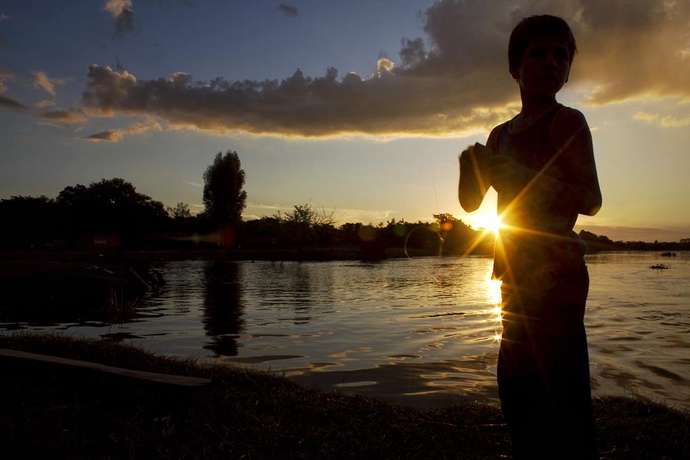 Preparandose para volver a casa, este niño enrolla su linea de pescar, despues de una jornada a orillas del Río Jejuí. (Puerto La Niña, San Pedro, Paraguay - Tetsu Espósito)