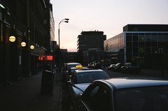 Evening Light (Caramel Covered Crack) Tags: street city sunset red silhouette yellow burlington reflections vermont streetlamp taxi 40mm vt f19 roundlamps
