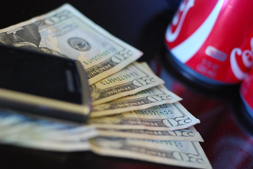 Money, cell phone and soda