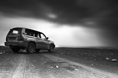 End of the road (MJ ) Tags: road bw cloud white motion black cars car rock canon eos rocks desert north toyota land 1855mm cruiser efs qatar 2010   of 40d