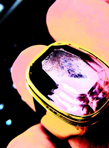Overexposed and saturated photo of a large amethyst ring on a hand