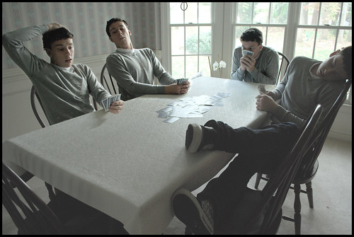 Four cloned peple playing a card game at a table. Multiplcity picture