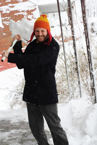 Smiling man shoveling snow.