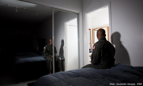 A black man sits on a bed. His back is to the camera and he is facing to the right. A mirror reflects his front but his face is obscured by a panel. He is in fatigues.