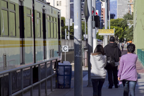 Pedestrians walk along side a Blue Line train in Downtown L.A.