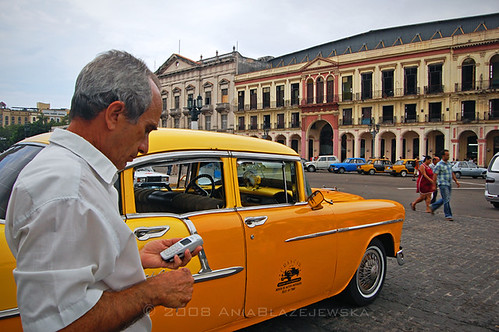 Cuba, Havana. Yellow taxi and its driver with a mobile phone. by Ania Blazejewska.