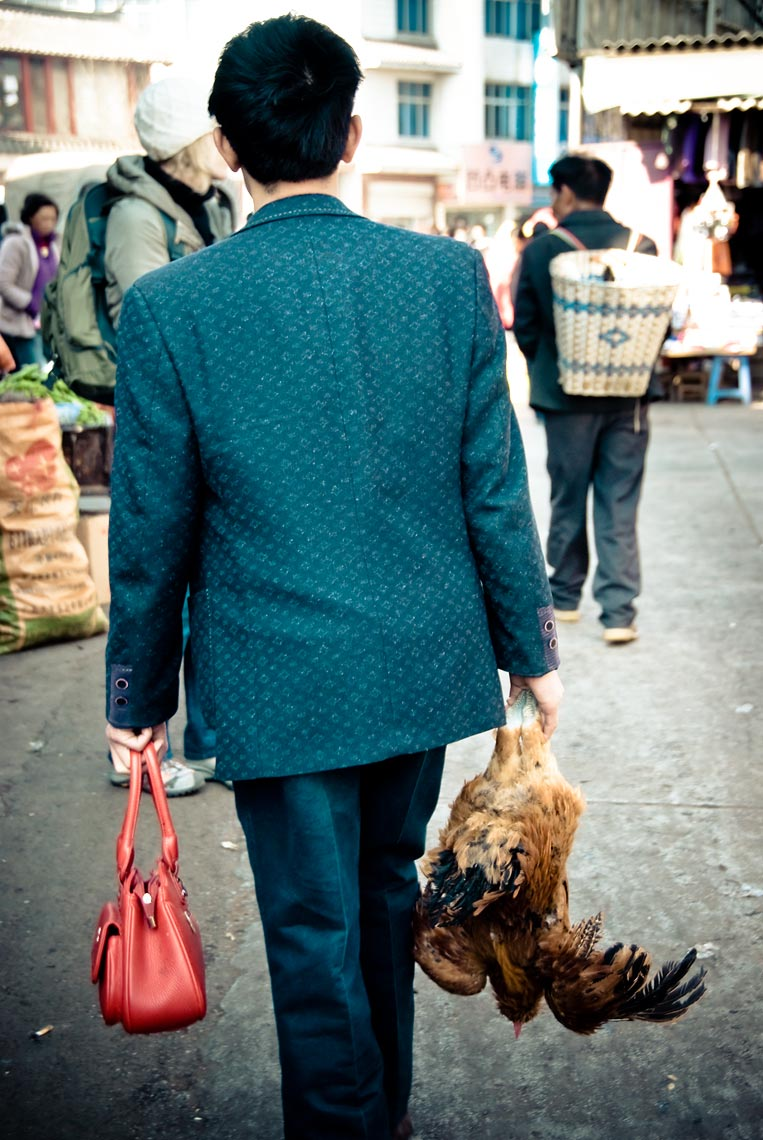 Man with Chicken and Red Purse: Man with red purse and live chicken, Li Jiang, Yunnan, China.