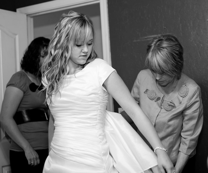 Bride getting on her bridal gown