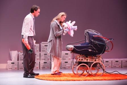 On-stage scene from the play. A man and woman stand looking into a pram, the woman with a many-limbed plush toy. The pram has a wild series of tubes and wires snaking out of it.