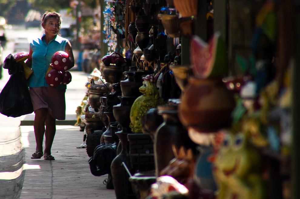Mujer alfarera atendiendo su local de ventas de alfarería y cerámica sobre la avenida principal La Candelaria, donde se encuentra todo tipo de artes y trabajos de alfarería, oficio emblemático de los artesanos de Areguá (Areguá, Paraguay - Elton Núñez)