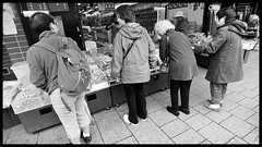 Stopping and shopping in Vancouver's Chinatown (Eric Flexyourhead) Tags: street city urban bw canada shop vancouver shopping blackwhite store women chinatown bc britishcolumbia chinese sidewalk storefront 169 shoppers penderstreet zd 918mm olympusep1 panasonicdmwma1