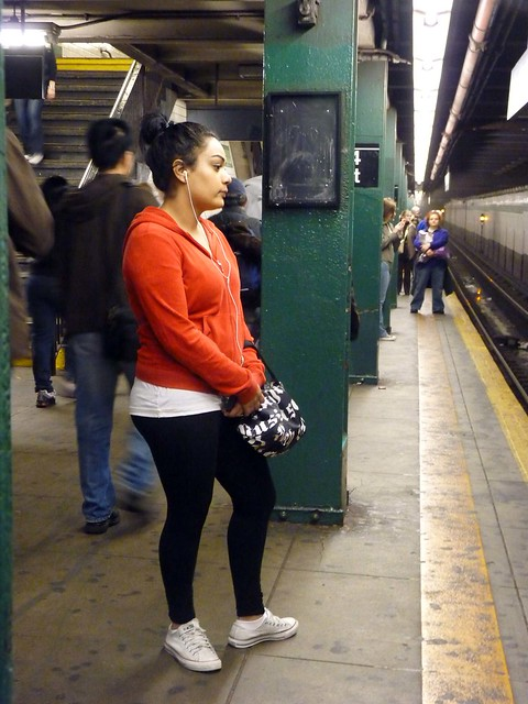 orange woman subway hoodie waiting pretty platform sneakers uptown headphones mta ftrain