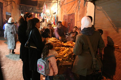 Photo of people buying grilled corn in Derb Dabachi street in the old Medina of Marrakech