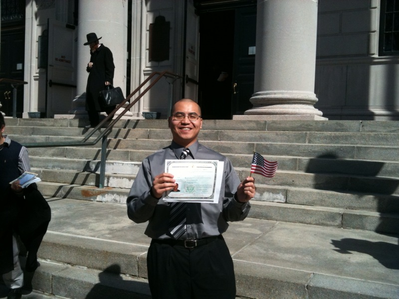 Me outside the courthouse with my naturalization certificate. It's a beautiful day.