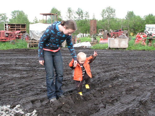 toddler walking in mud with tractors