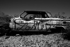 Impala (missiletest) Tags: blackandwhite bw abandoned car neglect digital canon graffiti desert decay nevada neglected chevy vacant ghosttown grayscale impala decrepit rhyolite desolate derelict 1022mm decayed decaying dilapidated rundown greyscale loveme 30d chevyimpala junkcar canon30d