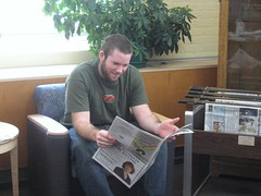 Student reading newspaper in library