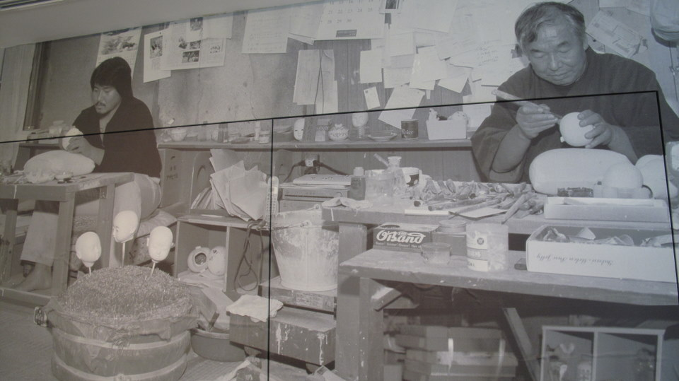 Black and white photos of the workers making dolls.