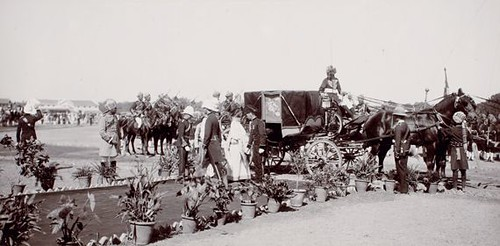 Showing the Begum of Bhopal who, having disembarked from her horse-drawn carriage, is being escorted down a path