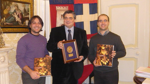 Il sindaco Ganau ci conferisce una targa e il libro sulla storia dei Candelieri, davanti al gonfalone del comune di Sassari