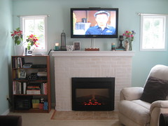 Oh, Hey Vern! (evsmama) Tags: brown white black window fireplace aqua candles teal bookshelf electronics shelving mantel hgtv whitepaint pointsettias flatscreentv vernyip capecodhome electricfireplaceinsert uglyrecliner